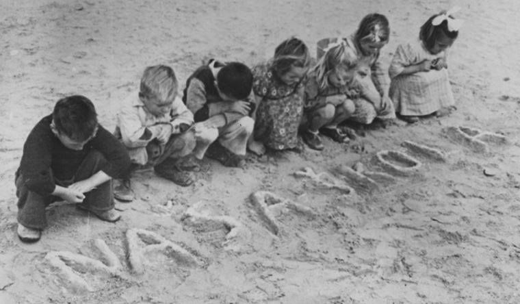"""Young children at a World War II refugee camp in Tolumbat, Egypt write the words """"naša škola,"""" or """"our school,"""" into the sand. 