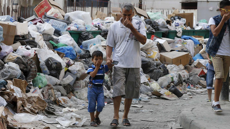 Residents cover their noses as they walk past garbage piles | Source: REUTERS
