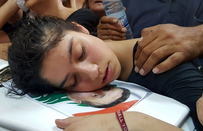 The daughter of a man who died in a suicide bomb attack in his village, mourns on his coffin during his funeral, June 29, 2016. Source: REUTERS/Hassan Abdallah