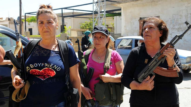 Women pose with guns in front of journalists in the Christian village of Qaa, where suicide bomb attacks took place on Monday Source: REUTERS/Hassan Abdallah