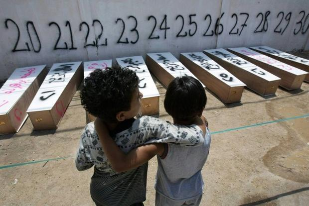 Children stand in front of the coffins of 72 people killed in Israeli air strikes in the southern Lebanese city of Tyre, on July 21, 2006 | Source: AFP/HassanAmmar