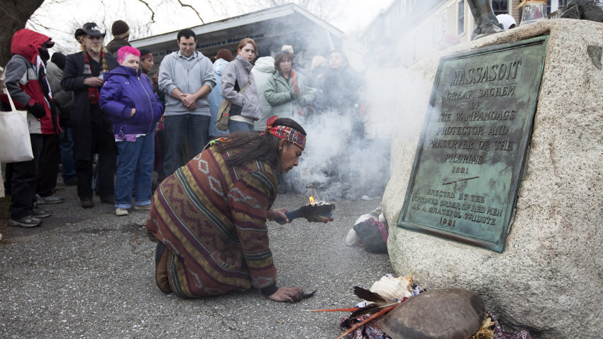 """Native American rekindles a small fire. The smoke symbolizing a ritual for healing and a connection with the """"creator.""""   Source: Boston.com"""